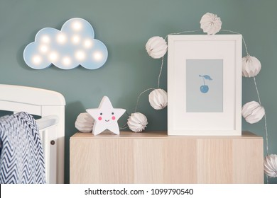 Stylish nursery interior with mock up photo frame , cotton lamps, star and blue cloud. Green background wall.