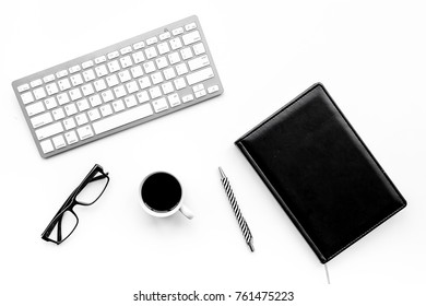 Stylish office desk. Trendy monochrome. Black notebook, glasses, pen and  coffeee on white background top view
