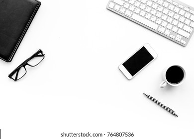 Stylish office desk. Trendy monochrome. Black notebook, glasses, pen, cell phone and  coffeee on white background top view copyspace