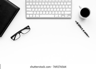 Stylish office desk. Trendy monochrome. Black notebook, glasses, pen and  coffeee on white background top view copyspace