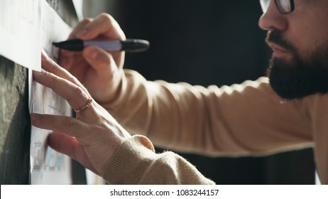 Stylish office in loft style. Businessman makes notes on the wall. Business idea, thinking design, mind map. Designer works in loft office and makes notes on the drawings on the wall. Close up