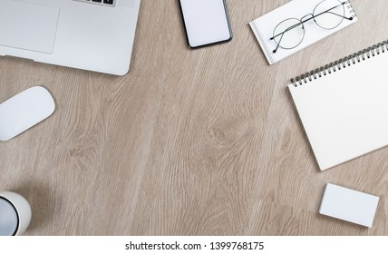 Stylish office table desk. Workspace with laptop, mouse, notepad, pencil, glasses, mobile phone and coffee on white oak wooden blackground. Flat lay, top view