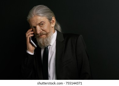 Stylish old male talking on cell phone. Elderly male in studio against black background holding mobile phone.