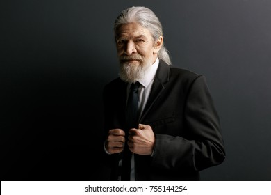 Stylish old man in black jacket. Portrait of whitebeard male with long grey hair on dark background.