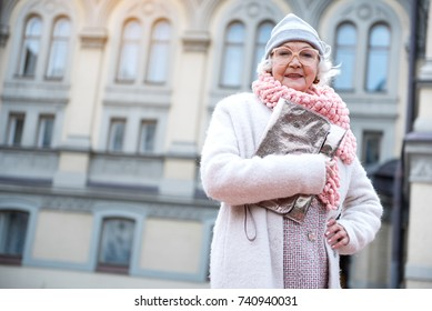 Stylish old woman standing on street