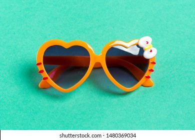 Stylish orange sunglasses in heart shape on mentol green background, flat lay. Space for text. Time to travel, Summer vacation concept and relax. holidays