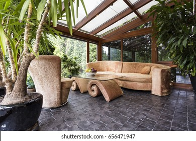 Stylish orangery with potted plants, glazed roof and unique velvet furniture