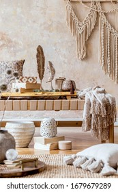 Stylish oriental living room with design beige chaise longue, beautiful macrame, pillows, wooden tray, carpet and elegant personal accessories in wabi sabi home decor.