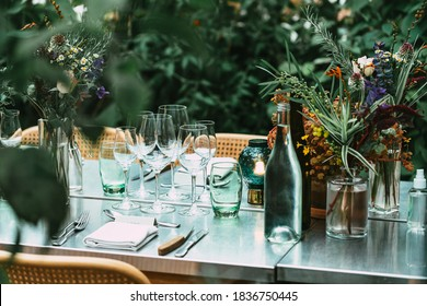 Stylish Outdoor Dinner Party. Decorated  Table with beautiful wild flower bouquets.