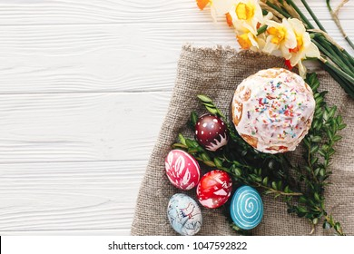 stylish painted eggs and easter cake on rustic wooden background with spring flowers and candle, top view. space for text. happy Easter concept, flat lay. seasons greetings