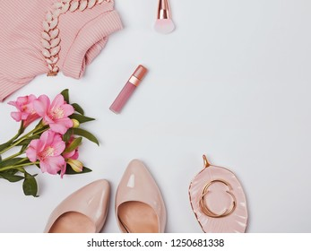Stylish pale pink feminine accessories and flowers on the white background.