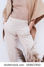 Stylish Pants and sweater. Details of everyday look. Model wearing casual beige outfit. Trendy minimalistic style. Beige aesthetics. Fashion look book. Warm Fall Winter seasons
