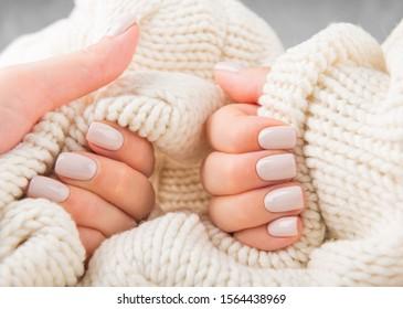 Ongles beiges pastel élégantes tenant du matériel de laine tricoté