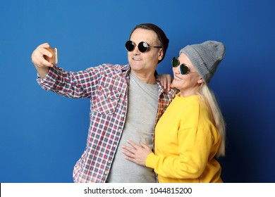 Stylish pensioners taking selfie on color background