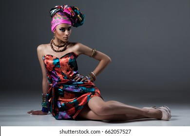 stylish photo of Fashion African/Libyan woman in silk colorful dress and in a turban, with bracelets earrings rings sitting on the floor, posing on gray background