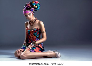 stylish photo of Fashion African/Libyan/Indian woman in silk colorful dress and in a turban, with bracelets earrings rings sitting on the floor, posing on gray background