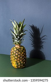Stylish pineapple set on a minimalistic photo studio background. Colors used are cool grey and dark green to contrast and compliment the warm colors of the pineapple.