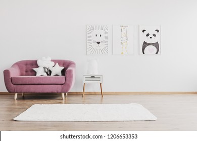 Stylish pink couch with cute pillows in spacious baby room interior with animals posters on the wall