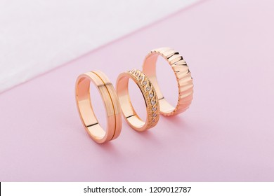 Stylish pink gold rings with different design on pink background. Product concept for jeweler