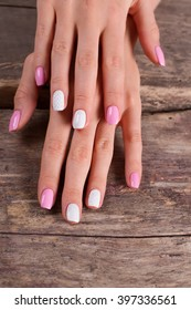 Stylish pink manicure on the old boards.