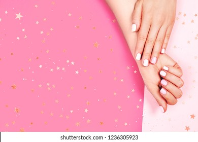 Stylish pink and white manicure on pastel background with sparkles and place for text.