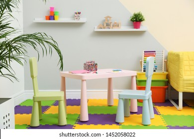 Stylish playroom interior with table, chairs and sofa