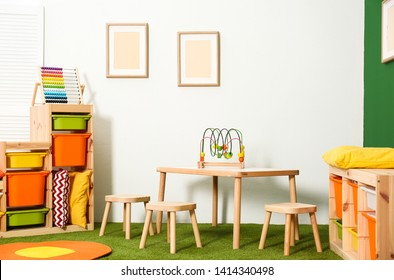 Stylish playroom interior with table and stools