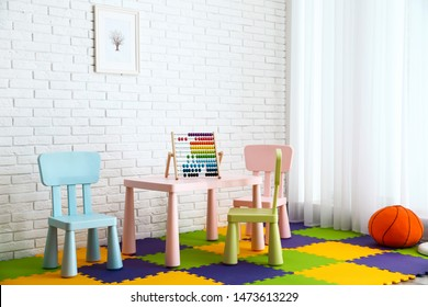 Stylish playroom interior with toys and modern furniture. Space for design