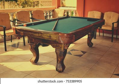 Stylish pool table with a cue and billiard balls on a nice patio. Snooker. Old photo. Stunning vintage. Matte background. Retro.