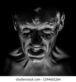Stylish portrait of adult caucasian man with very angry face and who seems like maniac or devil. Black and white shot, low-key lighting.