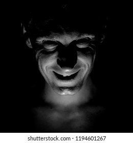 Stylish portrait of adult caucasian man. He smiles like maniac and seems like maniac or crazy. Black and white shot, low-key lighting.