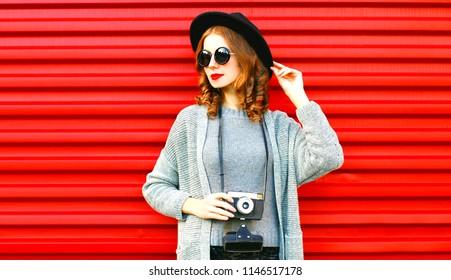 Stylish portrait autumn portrait woman holds retro camera on a red background