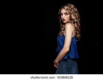 Stylish Portrait of a beautiful girl on a black background. Blonde in designer clothes. fashion Photo