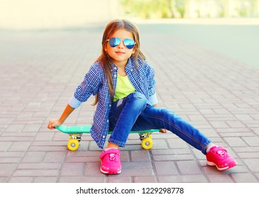 Stylish portrait smiling little girl sitting on skateboard on city street