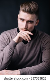 Stylish portrait of young handsome man holding his hands together and looking very confident and serious. Modern businessman in his thoughts. Attractive person working as a model for journals.