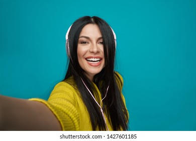 Stylish, positive model with long straight black hair listening music with headphones. Happy, beautiful girl with perfect smile posing on blue background, looking at camera, taking selfie.