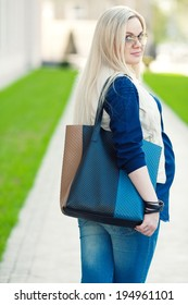 Stylish Pregnancy Concept. Portrait of a fashionable mommy with long blond hair wearing casual trendy clothes, eyewear and going shopping with blue leather bag. Sunny weather. Outdoor shot