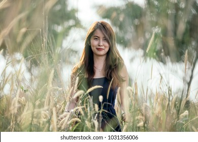 Stylish pretty asian woman with dimple with long brown curly hairs stand at dandelion field.