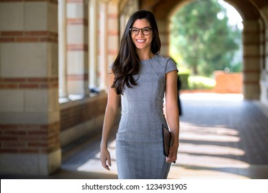 Stylish pretty female career professional in modern suit walking confidently to workplace