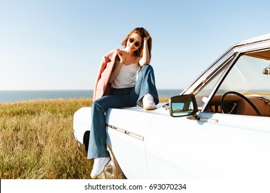 Stylish pretty woman relaxing while sitting on a car outdoors and looking at the landscape