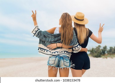 stylish pretty women on summer vacation on beach, bohemian style, friends together, fashion trend, accessories, happy emotion, positive mood, embracing, view from back, traveling, shorts, sexy