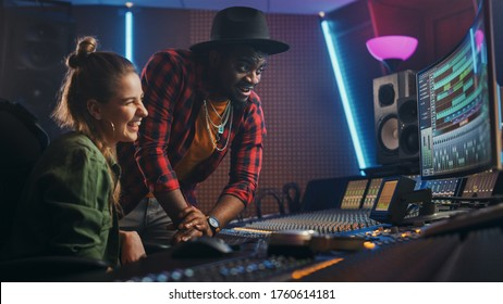 Stylish Producer and Audio Engineer Working together in Music Recording Studio on New Album, Talk, Use Control Desk Equalizer, Mixing Board and Software to Create Hit Song. Artist and Musician Collab