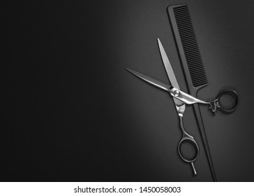 Stylish professional barber scissors, hair cutting shears on black background. Hairdresser salon equipment concept, hairdressing set. Haircut accessories. Copy space image, flat lay mockup