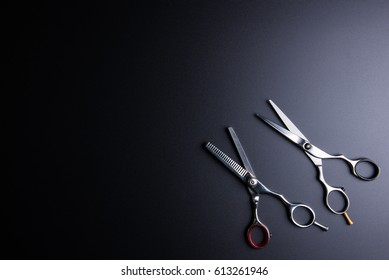 Stylish Professional Barber Scissors, Hair Cutting and Thinning Scissors on black background. Hairdresser salon concept, Hairdressing Set. Haircut accessories. Copy space image, flat lay