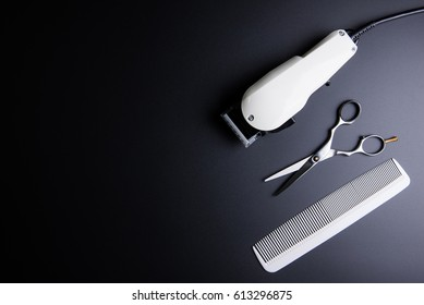 Stylish Professional Barber Scissors, White comb and White electric clippers on black background. Hairdresser salon concept, Hairdressing Set. Haircut accessories. Copy space image, flat lay