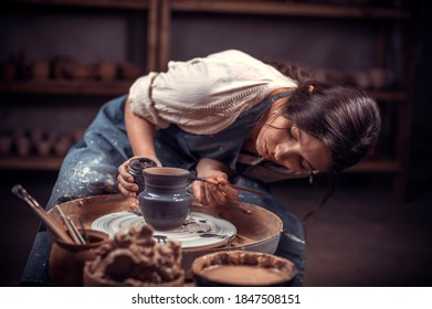 Stylish professional potter sculptor works with clay on a Potter's wheel and at the table with the tools. Craft production.