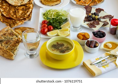 Stylish Ramadan (iftar) table.Traditional Turkish lentil soup in yellow soup set,fancy fabric napkin on the white table with other foods.Islamic holiday concept.
