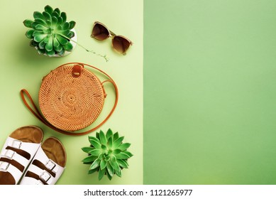 Stylish rattan bag, birkenstocks, succulent, sunglasses on green background. Banner. Top view with copy space. Trendy bamboo bag and white shoes. Summer fashion flat lay. Creative pop art design.