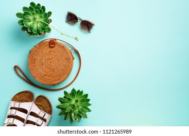 Stylish rattan bag, birkenstocks, succulent, sunglasses on blue background. Banner. Top view with copy space. Trendy bamboo bag and white shoes. Summer fashion flat lay. Creative pop art design.