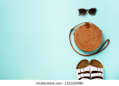 Stylish rattan bag, birkenstocks, sunglasses on blue background. Top view with copy space. Trendy bamboo bag and white shoes. Summer fashion flat lay. Creative pop art design.
